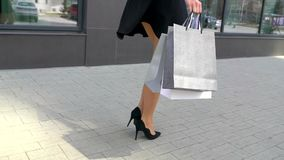 Sale, consumerism: Confident lady with shopping bags walking in a city. Female legs in high heels shoes walking in the