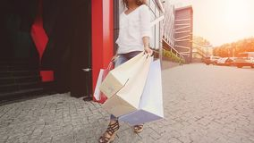 Sale, consumerism: Confident lady with shopping bags walking in a city. Slow motion. sunshine background.  stock video