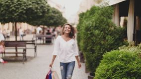 Sale, consumerism: Confident lady with shopping bags walking after shopping time in a city.  stock video footage