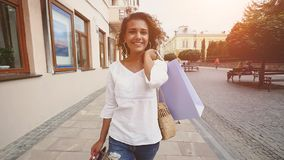 Sale, consumerism: Confident lady with shopping bags walking after shopping time in a city. Slow motion.  stock footage