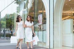 Sale, consumerism och folkbegrepp - lyckliga unga kvinnor med shoppingpåsar på stadsgatan arkivbild