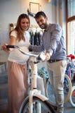 Sale, consumerism och folkbegrepp - par som väljer den nya cykeln royaltyfri fotografi