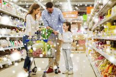 Family with food in shopping cart at grocery store. Sale, consumerism and people concept - happy family with child and shopping cart buying food at grocery store royalty free stock photo