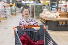 Sale, consumerism and people concept - happy little girl with food in shopping cart at grocery store.  Stock Image