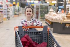 Sale, consumerism and people concept - happy little girl with food in shopping cart at grocery store.  Royalty Free Stock Photos