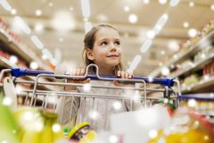 Girl with food in shopping cart at grocery store. Sale, consumerism and people concept - happy little girl with food in shopping cart at grocery store or Royalty Free Stock Photo