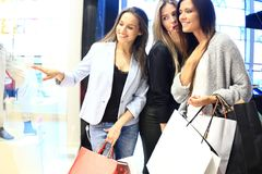 Sale, consumerism and people concept - happy surprised young women with shopping bags pointing finger to shop window Royalty Free Stock Photography