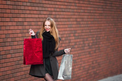 Sale, consumerism and people concept - happy young beautiful women holding shopping bags, walking away from shop. Stock Photos