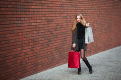 Sale, consumerism and people concept - happy young beautiful women holding shopping bags, walking away from shop. Royalty Free Stock Photos