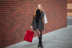 Sale, consumerism and people concept - happy young beautiful women holding shopping bags, walking away from shop. Sale, consumerism and people concept - happy Royalty Free Stock Images