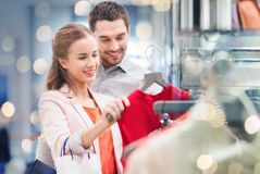 Happy young couple choosing dress in mall Stock Images