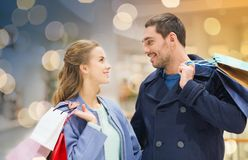 Happy young couple with shopping bags in mall. Sale, consumerism and people concept - happy young couple with shopping bags talking in mall royalty free stock photos