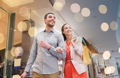 Happy young couple with shopping bags in mall. Sale, consumerism and people concept - happy young couple with shopping bags walking in mall royalty free stock images