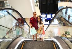 Sale, consumerism and people concept - happy young couple with shopping bags walking in mall. Sale, consumerism and people concept - happy young couple with Stock Image