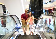 Sale, consumerism and people concept - happy young couple with shopping bags walking in mall. Sale, consumerism and people concept - happy young couple with Royalty Free Stock Photos