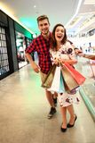 Sale, consumerism and people concept - happy young couple with shopping bags walking in mall. Royalty Free Stock Photos