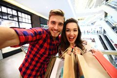 Sale, consumerism and people concept - happy young couple with shopping bags walking in mall. Stock Photos
