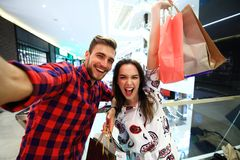 Sale, consumerism and people concept - happy young couple with shopping bags walking in mall. Sale, consumerism and people concept - happy young couple with royalty free stock images