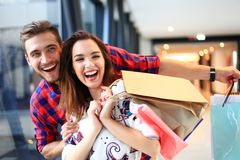 Sale, consumerism and people concept - happy young couple with shopping bags walking in mall. Sale, consumerism and people concept - happy young couple with royalty free stock image