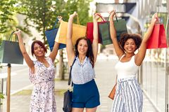 Happy women with shopping bags on city street stock photo