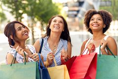 Happy women with shopping bags on city street royalty free stock image