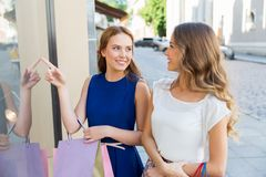 Happy women with shopping bags at storefront Royalty Free Stock Images