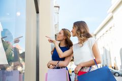 Happy women with shopping bags at storefront Stock Image