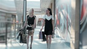 Sale, consumerism and people concept - happy young women with shopping bags walking along shopping mall, fashion student. Sale, consumerism and people concept stock video footage