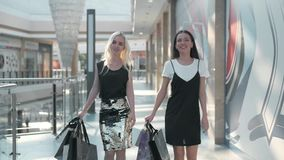 Sale, consumerism and people concept - happy young women with shopping bags walking along shopping mall, fashion student. Sale, consumerism and people concept stock video