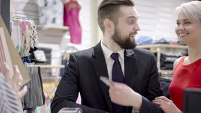 Sale, consumerism, shopping and people concept - happy couple with credit card at clothing store in mall. Sale, consumerism, shopping and people concept - happy stock footage