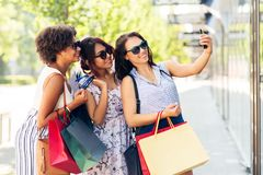 Women with shopping bags taking selfie in city royalty free stock images