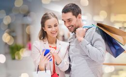 Couple with smartphone and shopping bags in mall Royalty Free Stock Image