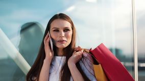 Sale, consumerism: Young woman with smartphones and shopping bags standing and talking near shopping centre stock video footage
