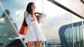 Sale, consumerism: Young woman with smartphones and shopping bags standing and talking near shopping centre stock footage