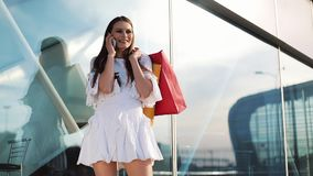 Sale, consumerism: Young woman with smartphones and shopping bags standing and talking near shopping centre.  stock footage