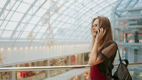 Sale, consumerism: Young woman with smartphones and shopping bags standing and talking near shopping centre.  stock video footage