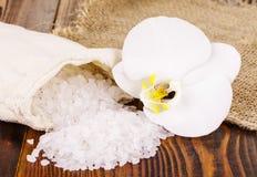 Sale da bagno bianco e una borsa con Orhid su superficie di legno immagini stock