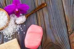 Sale da bagno bianco in una ciotola di legno con un cucchiaio, sapone, tela da imballaggio e fotografia stock