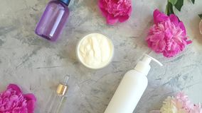 Sale da tavola cosmetico crema del fiore della peonia sul movimento lento concreto grigio del fondo video d archivio