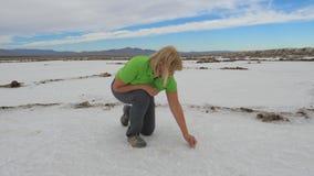 Sale di prove della donna da avere un sapore sedentesi su una superficie bianca di un lago asciutto nel deserto Fotografia Stock