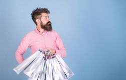 Sale and discount concept. Hipster on serious face carries shopping bags. Man with beard and mustache works as shop. Assistant, light blue background. Guy stock photos
