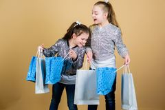 Sale and discount. Shopping day. Children hold bunch packages. Kids fashion. Expect more. Pay less. Girls sisters. Friends with shopping bags beige background stock image