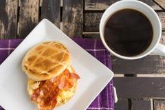 Sale el mollete con los huevos revueltos, el tocino y el queso en la placa blanca Fotografía de archivo libre de regalías