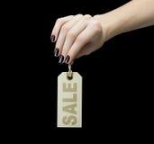 Sale etikett på kvinnahanden Arkivfoto