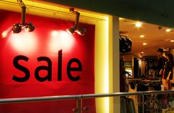 Sale, fashion apparel shop. A photograph showing the large word sale in the window of a fashionable apparel shop inside a modern shopping centre. Shop interior stock images
