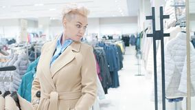 Sale, fashion, consumerism and people concept - woman shopping bags choosing clothes in mall or clothing store. stock video footage
