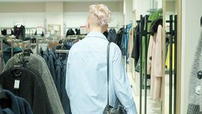 Sale, fashion, consumerism and people concept - woman shopping bags choosing clothes in mall or clothing store. stock video