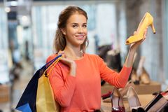 Happy young woman choosing shoes at store. Sale, fashion and people concept - happy young woman with shopping bags choosing shoes at store Stock Photo