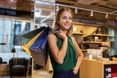 Happy young woman with shopping bags at shoestore Stock Images