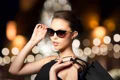 Woman in shades with shopping bags at christmas Royalty Free Stock Image
